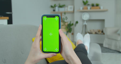 Woman at Home Lying on a Couch using Smartphone with Green Mock-up Screen, Doing Live Action