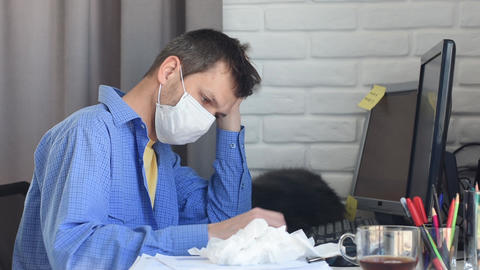 A sick quarantined medical mask employee works on a computer Live Action