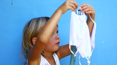 The girl hangs new masks on a hook. Help others Live Action