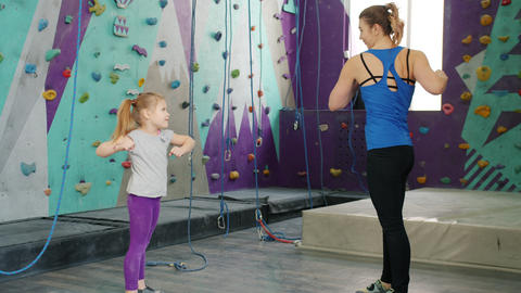 Little girl exercising indoors in climbing gym with loving mother twisting body Live Action