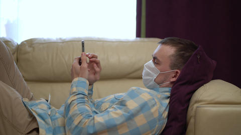 Man in a Medical Mask Uses a Smartphone at Home During Quarantine Live Action