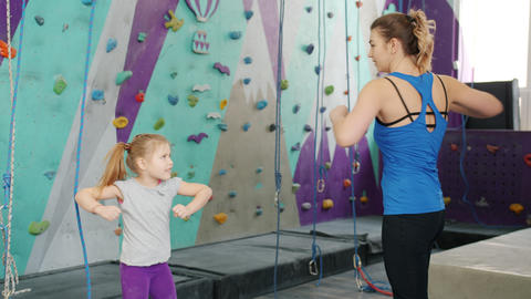 Slow motion of mother and daughter warming-up before climbing wall in indoor gym Live Action