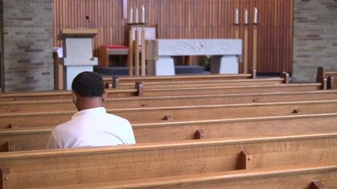 Sad man sits alone praying in a church Footage