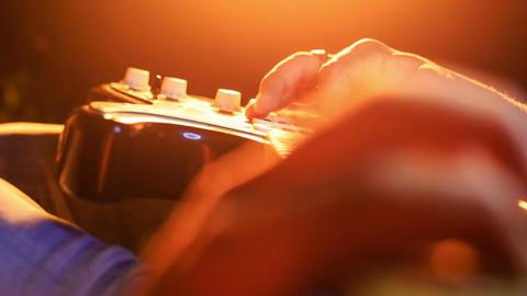 Guy Runs Fingers over Strings of Horizontal Guitar Closeup Footage