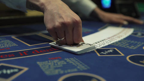 Dealer beautifully lays out cards on the card table in the casino Live Action