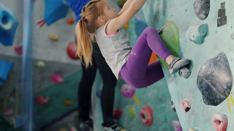 Adorable little girl climbing up colorful manmade wall training in indoor gym Live Action