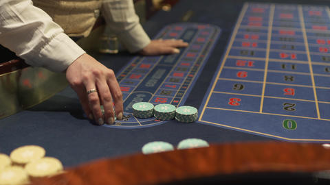 Dealer works in the casino moving chips with his hands at the gaming table Live Action