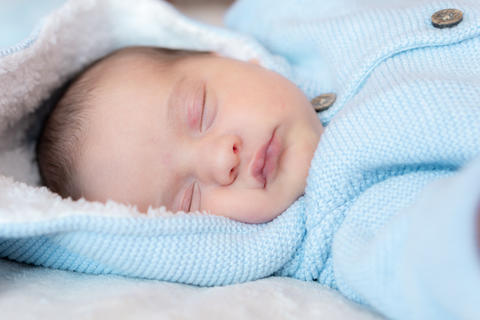 Newborn baby close-up. Side view of a newborn baby sleeping soundly on his back Photo