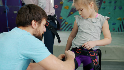 Friendly climbing instructor helping child with safety harness indoors in gym Live Action