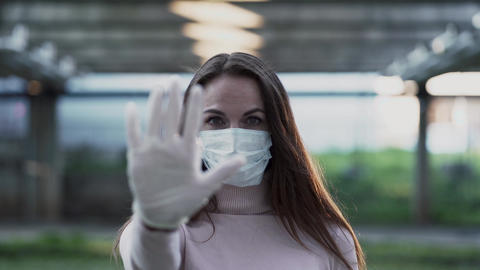 Young girl in medical mask and gloves shows stop sign Live Action