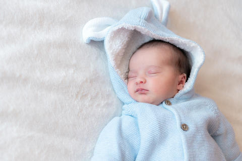 Newborn baby close-up, place for text. Newborn sleeping on his back in a blue Photo