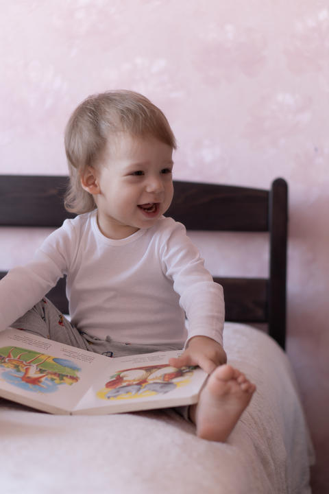 A little blond-haired boy is sitting on the bed and smiling, holding a book in Photo