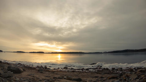 Thin ice layer moving at freezing shore during sunset. Time lapse shot Live Action