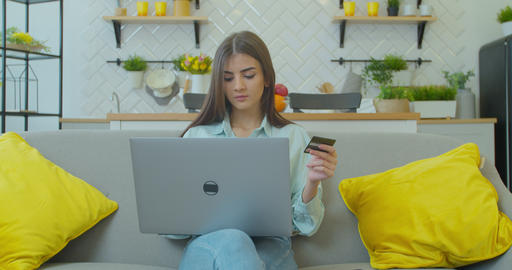 Pretty girl is making online payment holding bank card using modern laptop at Live Action
