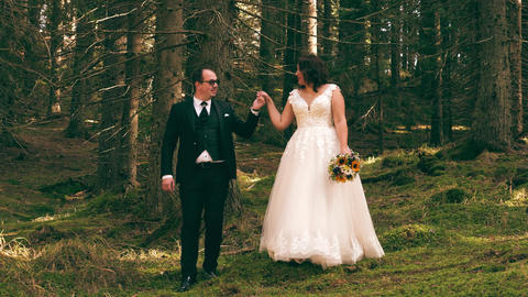 Bride and groom walking on the forest Live Action