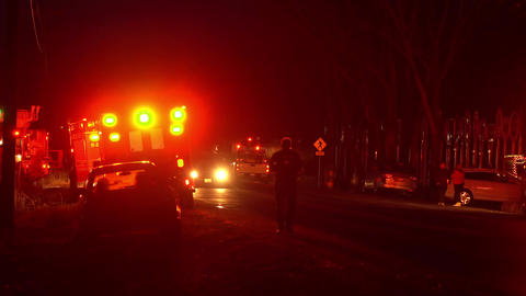 Person walking down street at night as lights from ambulance flashes Live Action