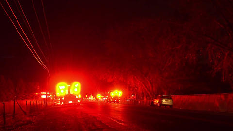 Emergency vehicles surrounding the road at night as lights flash Live Action