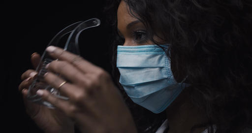 Portrait of a young female wearing a protective mask and glasses in a laboratory Live Action