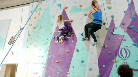 Slow motion of female climbers enjoying indoor climbing in gym supported by Live Action