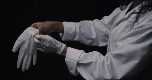 Doctor puts on protective surgical gloves Live Action