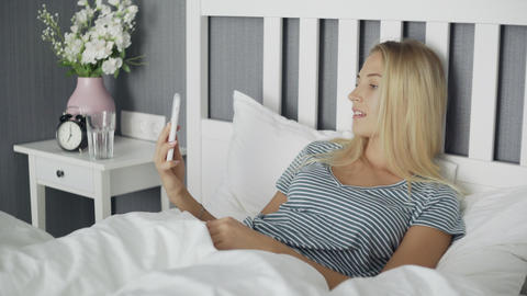 Smiling Young Woman lying on the Bed in Comfortable Bedroom and Taking Selfie Live Action