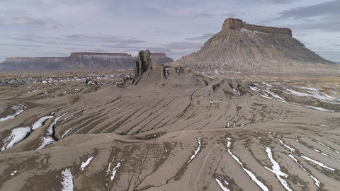 Flying low through eroded desert towards Factory Butte in Utah Live Action