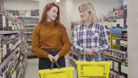 Blond and redhead Caucasian women with shopping baskets posing in wine shop Live Action