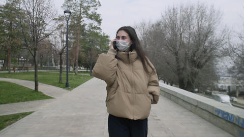 Beautiful woman with Medical Mask walking and talking on phone in the center of Live Action