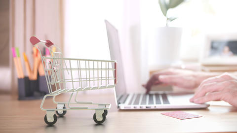 EBAY logo on boxes in shopping cart near the laptop. Editorial online shopping Live Action