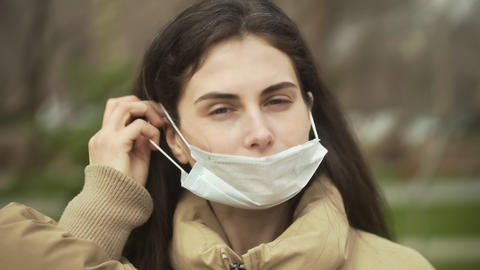 Young woman outdoors wearing medical face mask for protection of virus. Concept Live Action