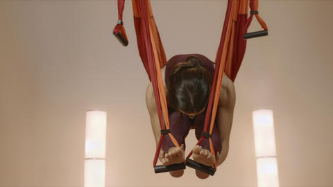 Girl practicing antigravity yoga at studio. Lady stretching body in hammock Live Action