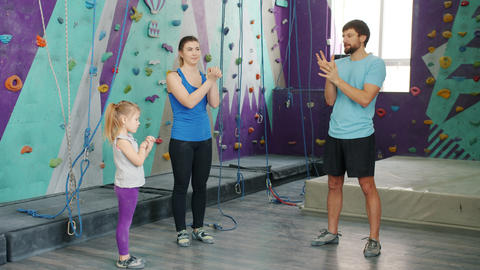 Young family mother, father and daughter warming-up in climbing gym together Live Action