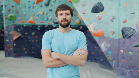 Portrait of handsome young sportsman standing in climbing facility indoors Acción en vivo