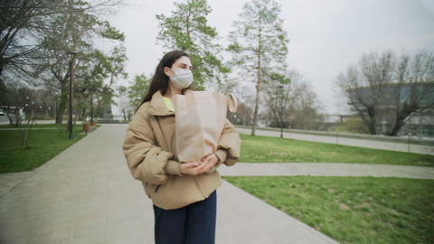Young Woman Wearing Protective Mask walks with Shopping bag During Coronavirus Live Action