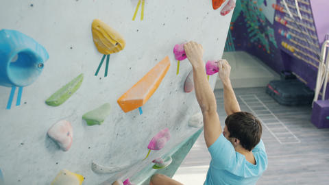 High angle view of young male adult climbing up bright artificial wall in gym Live Action