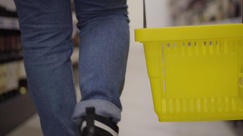 Close-up of unrecognizable person in jeans walking along supermarket shelves Live Action