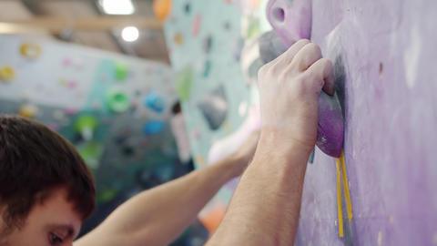 Close-up of strong young man moving up artificial climbing wall in indoor center Acción en vivo