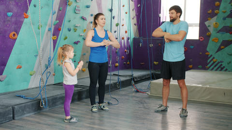Man and woman training in climbing gym with little daughter warming-up hands Live Action