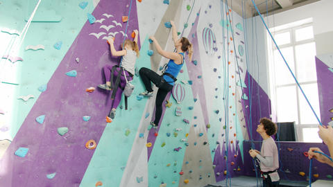 Woman and kid enjoying climbing in gym while companions holding ropes standing Live Action