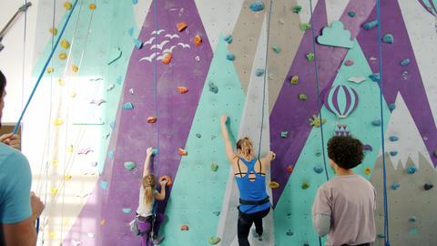 Slow motion of mother and daughter climbing wall in gym with support of belayers Live Action