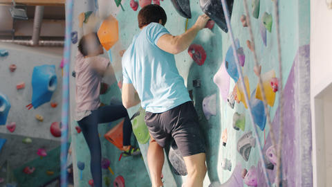 Man and woman training in rock-climbing facility indoors enjoying workout Live Action
