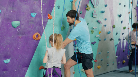 Father and daughter talking in rock-climbing gym ready to climb up artificial Live Action