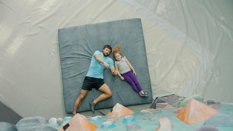 Top view of father and daughter lying on pad in climbing gym discussing rock Live Action