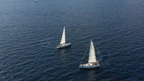 Two sailing yachts closely to each other, youth have fun on yachts, young people Live Action
