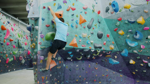 Sporty guy training in indoor climbing gym moving up wall holding artificial Acción en vivo
