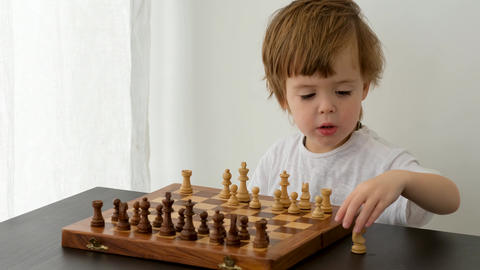 Cute little boy playing chess Acción en vivo