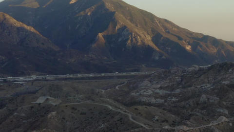 AERIAL: Over California Country Side with Highway and Mountains at Sunset Live Action
