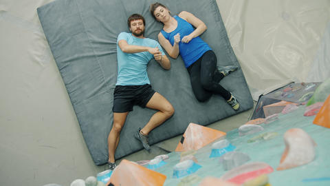Top view of man and woman discussing indoor climbing lying on pad pointing at Acción en vivo