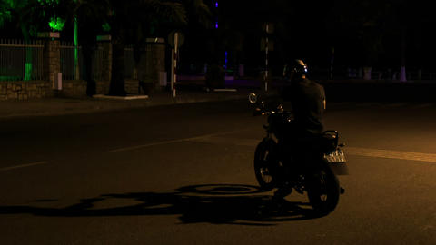Guy in Helmet Rides Motorcycle along Dark Street Footage