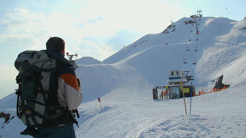 Tourist with backpack looking at snowy skiing run on mountains Footage